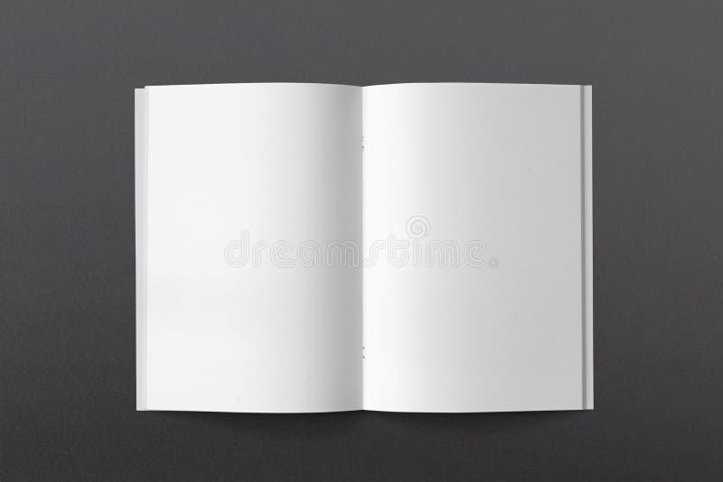 被打开的杂志或小册子在黑纸 空白页顶视图 库存图片