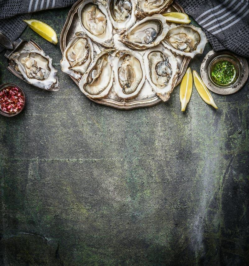 被打开的牡蛎用柠檬和各种各样的调味汁在土气背景,顶视图 免版税库存照片