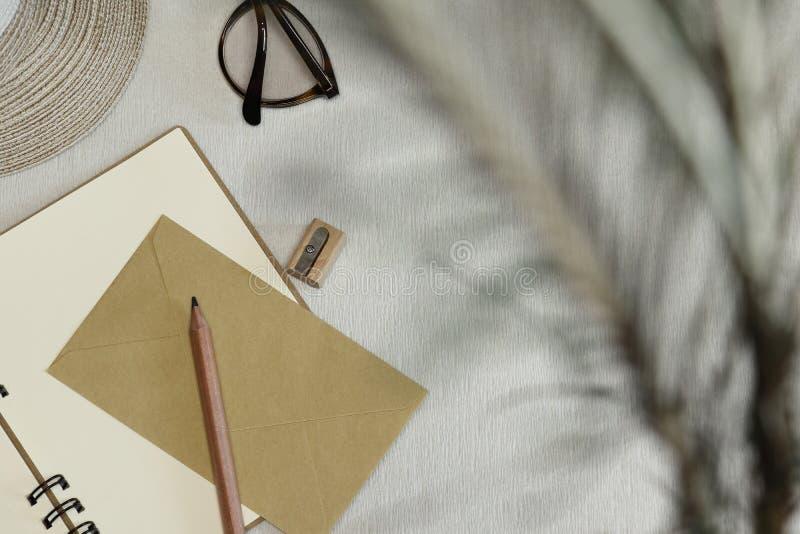 被打开的笔记本、铅笔、磨削器、信封、眼镜、帽子在桌上和阴影 免版税库存照片