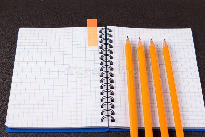 被打开的笔记薄和五颜六色的铅笔在黑背景 免版税库存照片