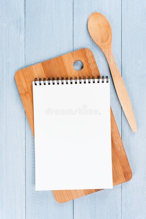 被打开的笔记薄和厨房器物空白纸在蓝色w的 免版税库存照片