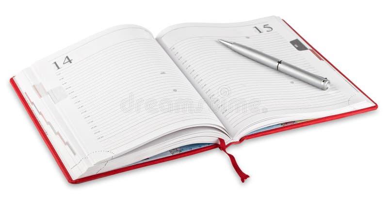 被打开的红色日志和笔 免版税库存图片