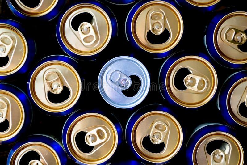 被打开的铝罐的抽象样式,顶视图 站立在黄色和蓝色罐头中的一个白色苏打或啤酒罐 免版税图库摄影