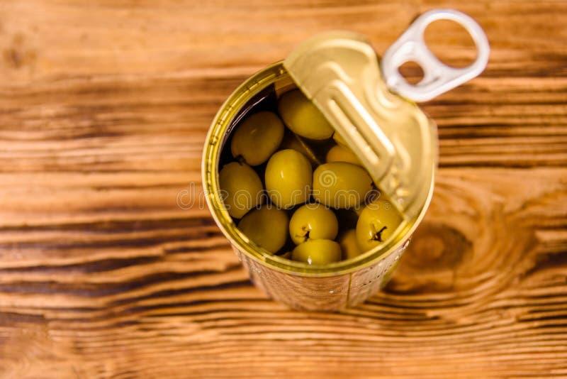 被打开的锡罐用在木桌上的绿橄榄 免版税库存图片