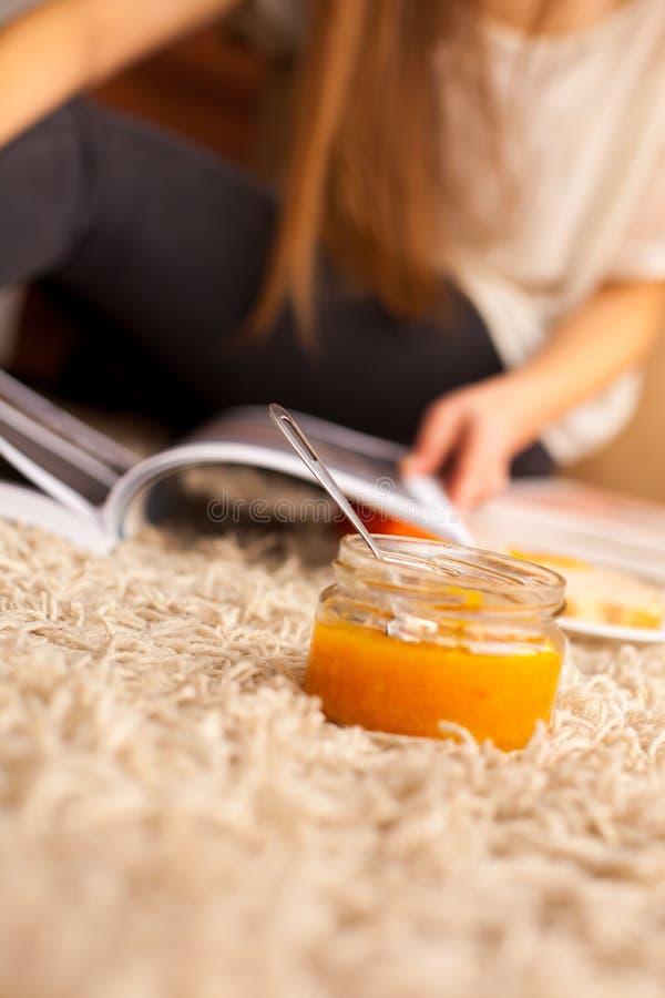 被打开的玻璃瓶子用甜杏子果酱在地板上 库存照片