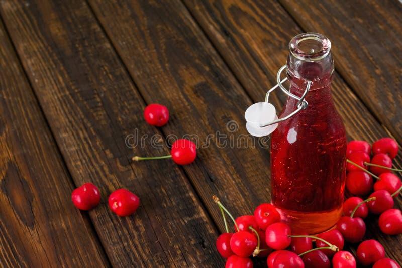被打开的玻璃瓶用在几棵樱桃中的果子柠檬水 库存图片