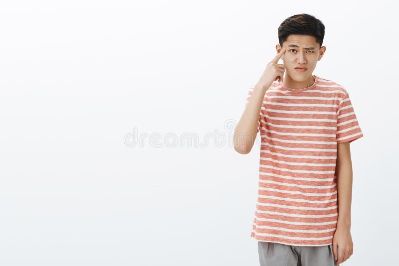 被打扰的和生气的逗人喜爱的亚洲男学生辗压食指画象在起反应寺庙弯身的肩膀附近的 免版税库存图片