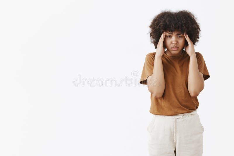 被打扰的强烈的不快乐的非裔美国人的妇女室内射击有握在寺庙的卷曲非洲的发型的手 免版税库存照片