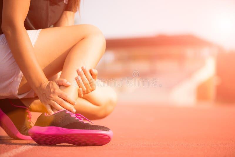 被扭伤的脚腕 遭受脚踝受伤的少妇 库存照片