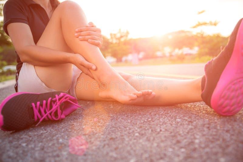 被扭伤的脚腕 遭受脚踝受伤的少妇 免版税库存图片