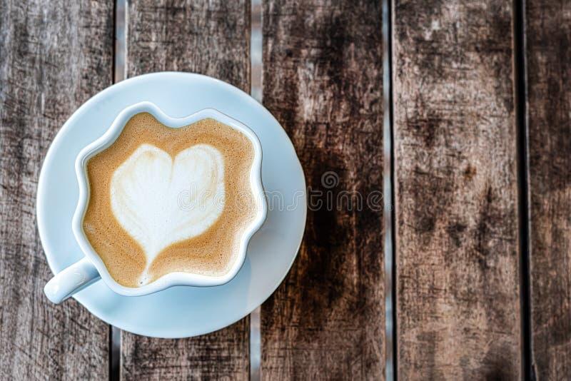 被扭屈的杯子与被绘的心脏的热奶咖啡咖啡在一张木织地不很细桌上站立 r 自由倒空 库存照片