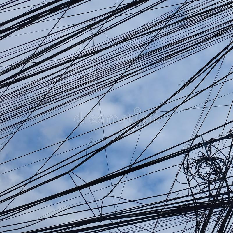 被扭转的输电线,多云天空作为背景 免版税库存照片