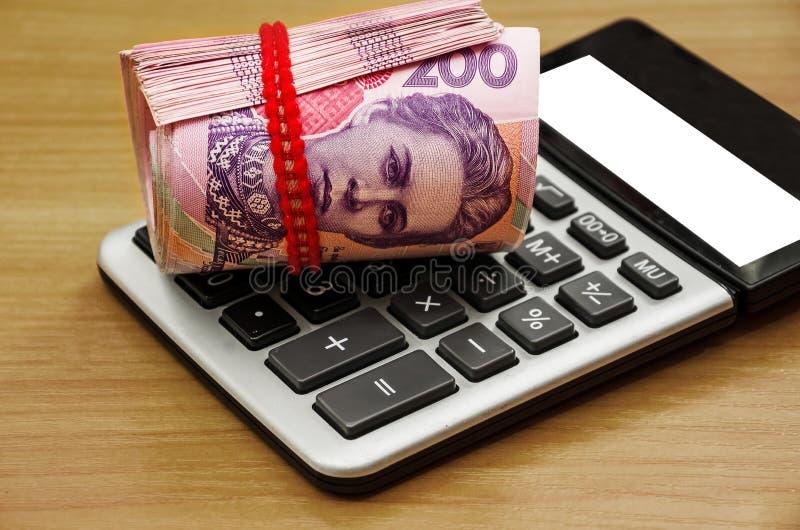 被扭转的200 hryvnia和一个计算器在一张木桌上 r 免版税库存图片