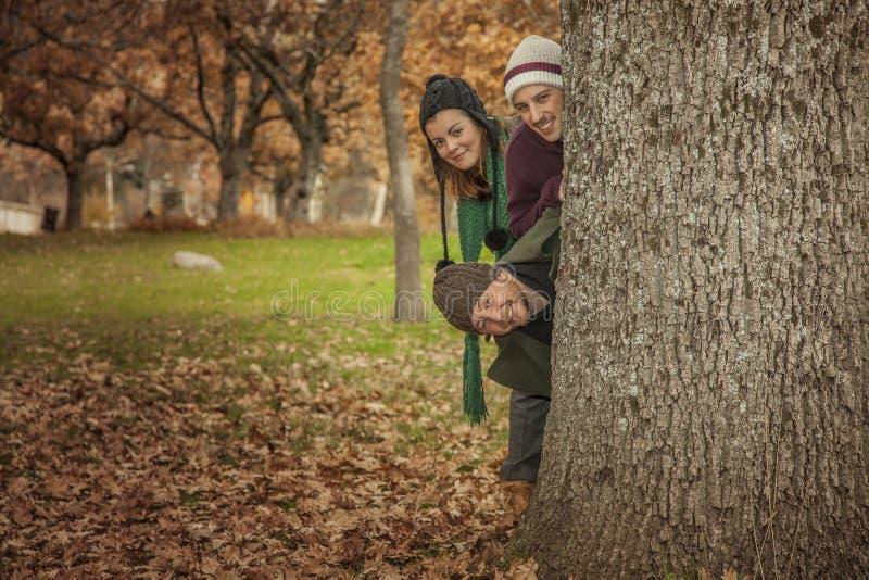 被投入的三个年轻成人在树后前往 充分地板地方教育局 免版税库存图片