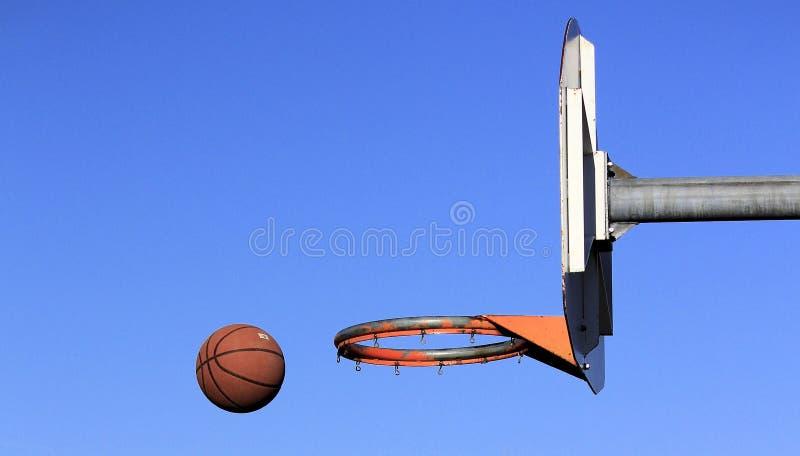 被投掷在箍的篮球在一个室外法院 免版税库存照片