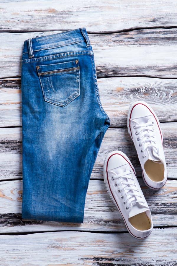 被折叠的牛仔裤和白色鞋子 免版税库存图片