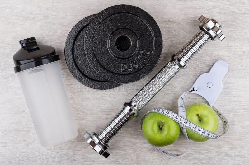 被拆卸的哑铃、塑料振动器、绿色苹果和措施 免版税库存照片
