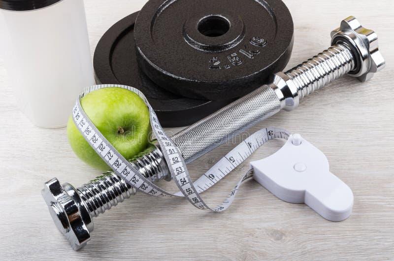 被拆卸的哑铃、绿色苹果和措施磁带 库存照片