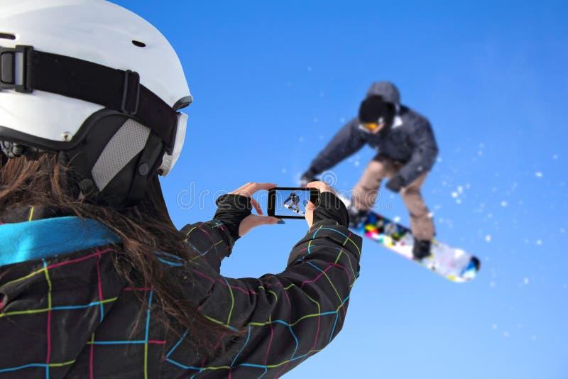 被拍摄的挡雪板跳与手机 库存图片