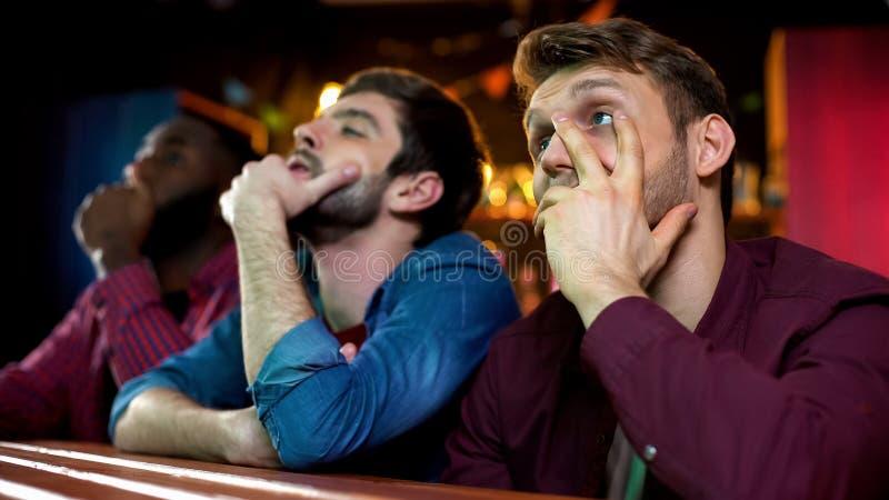被挫败的男性朋友在竞争,酒吧中弄翻了与喜爱的队损失 库存照片