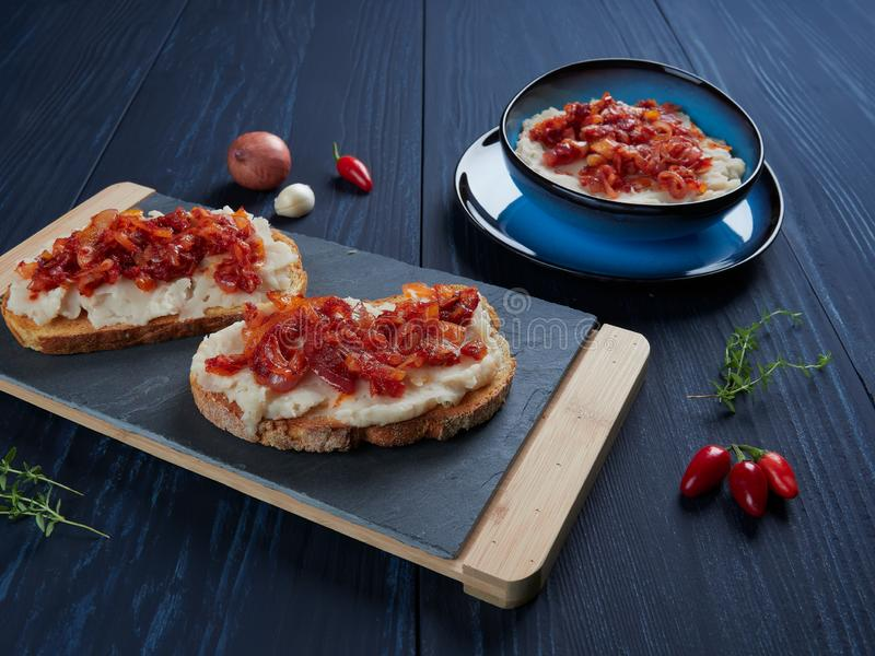 被捣碎的豆传播了与大蒜和菜油,与嫩煎的葱和西红柿酱罗马尼亚语顶部:fasole batuta 免版税库存图片