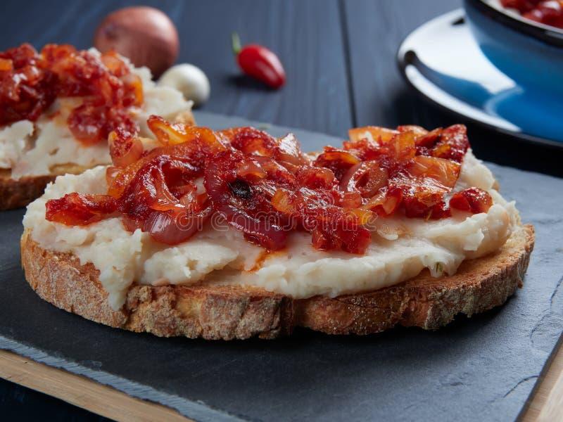 被捣碎的豆传播了与大蒜和菜油,与嫩煎的葱和西红柿酱罗马尼亚语顶部:fasole batuta 图库摄影