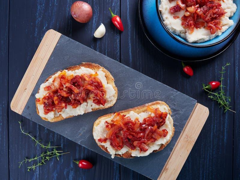 被捣碎的豆传播了与大蒜和菜油,与嫩煎的葱和西红柿酱罗马尼亚语顶部:fasole batuta 库存图片