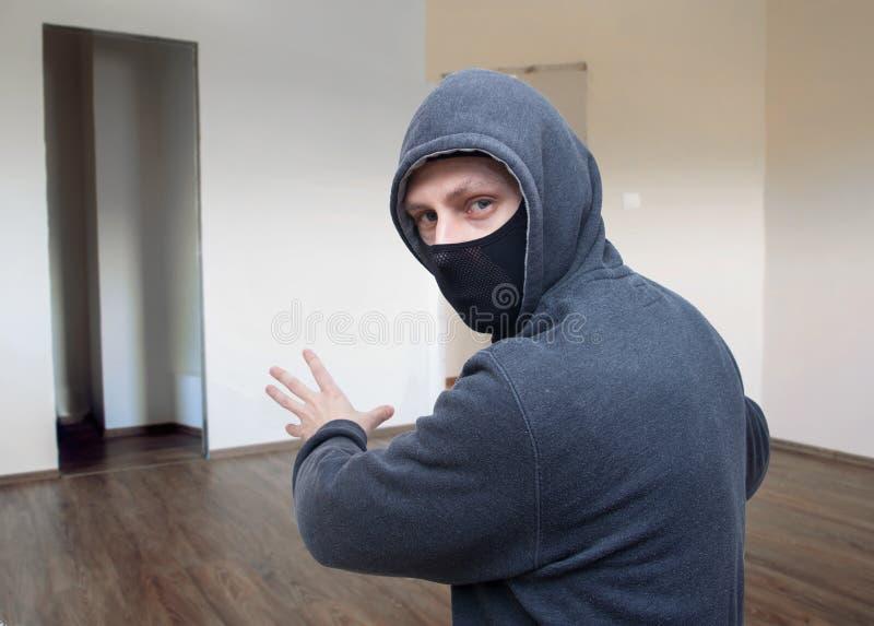 被掩没的窃贼在房子里 库存图片