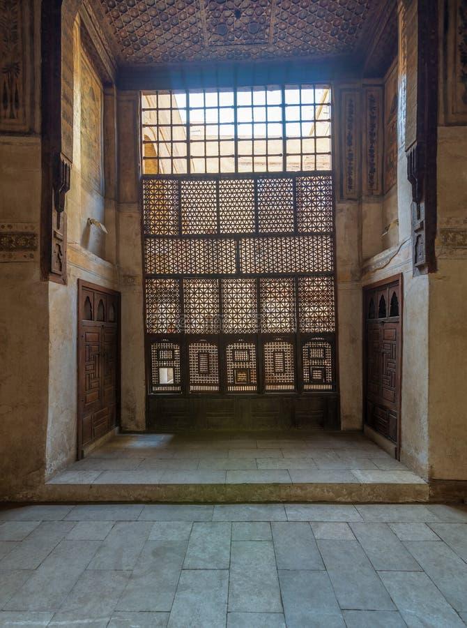 被插入的木窗口Mashrabiya和在无背长椅历史的Waseela Hanem议院,老开罗,埃及的木装饰的天花板 库存照片