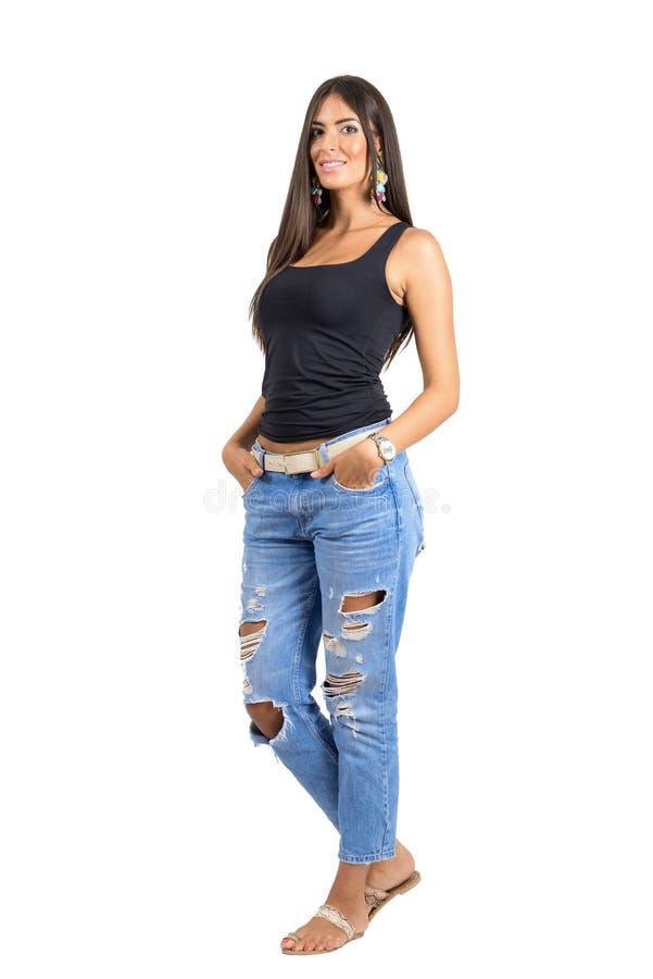 被撕毁的牛仔裤的年轻美丽的偶然妇女微笑对照相机的用在口袋的手 免版税库存照片