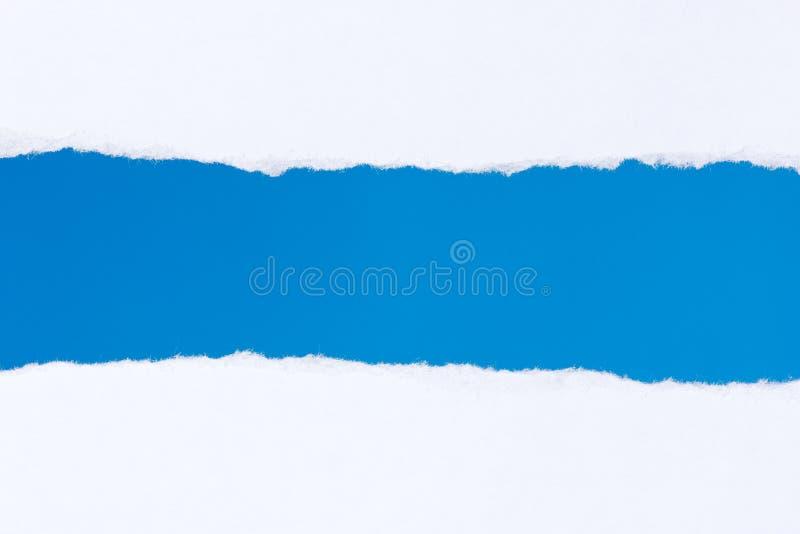 被撕毁的白皮书有蓝色背景 免版税库存图片
