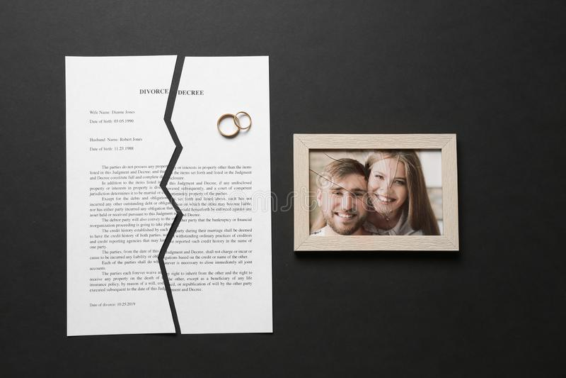 被撕毁的离婚旨令、圆环和残破的框架与照片在黑暗的背景 库存照片
