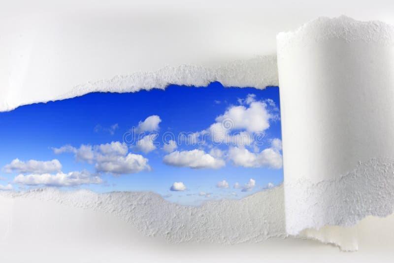 被撕毁的纸在蓝天 库存照片