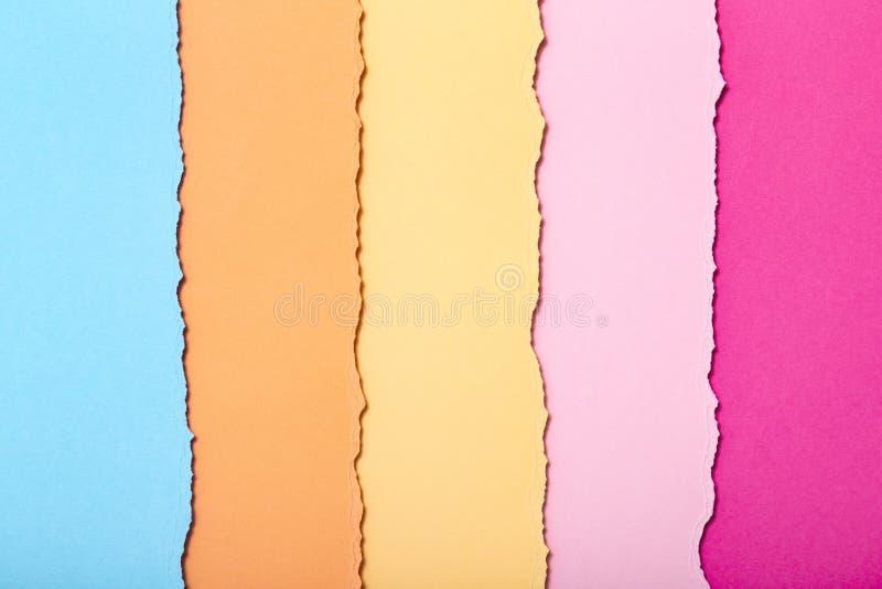 被撕毁的纸板多彩多姿的条纹抽象背景垂直说谎,顶视图 库存图片
