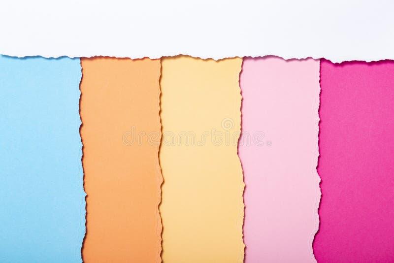 被撕毁的纸板多彩多姿的条纹抽象背景垂直说谎,顶视图 库存照片