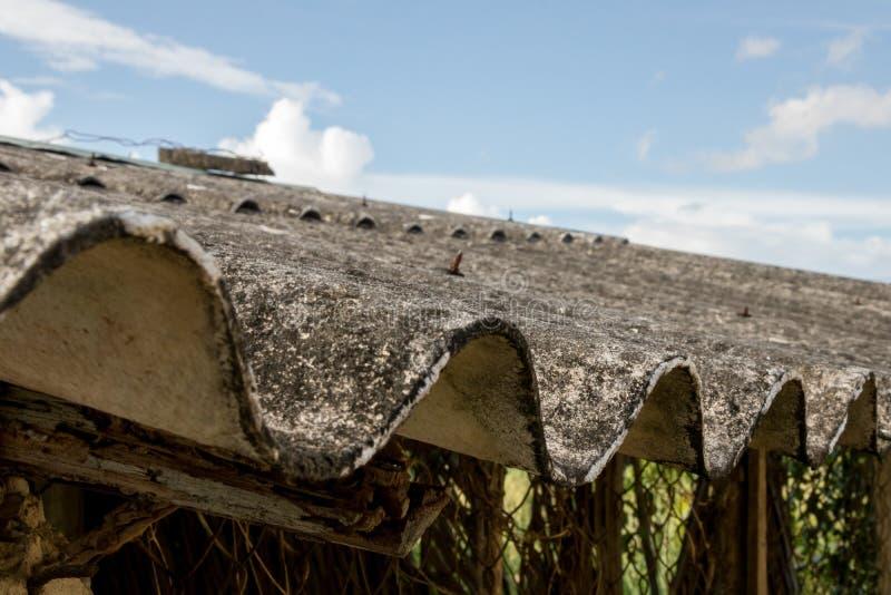 被放弃的亚洲鸡舍特写镜头肮脏的发霉的波纹状的屋顶有生锈的铁丝网的-与云彩的蓝色明亮的天空 库存照片