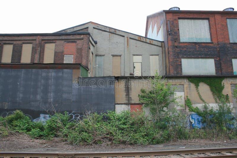 被放弃的制造的大厦与被绘的层数和上在火车轨道后的Windows与多云天空 免版税库存照片