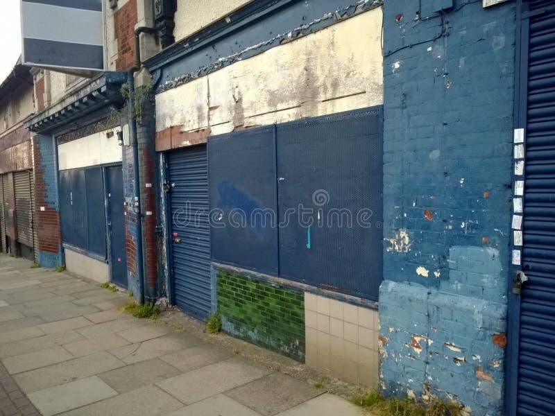 被放弃的商店行有上的商店朝向与粉碎的门面和剥在都市街道的蓝色油漆 库存图片
