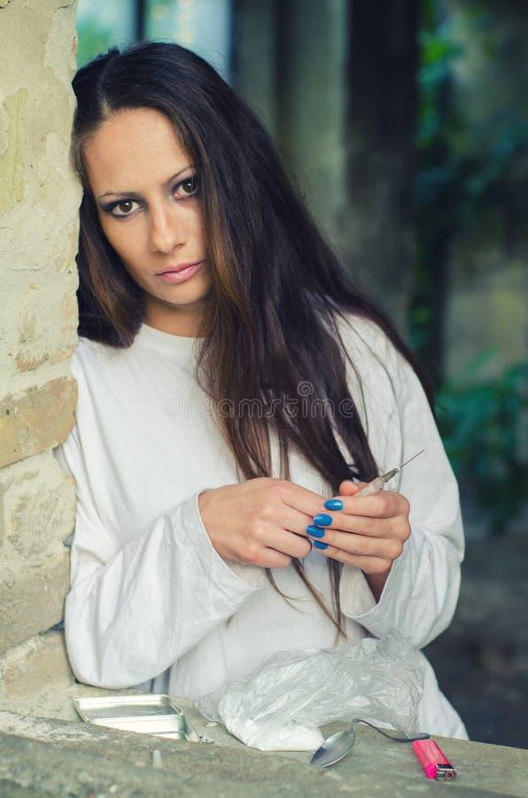被放弃的大厦的年轻女性药物吸毒者 库存照片