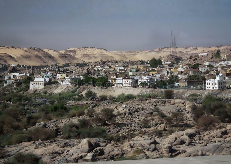 被放弃的小屋和房子由海水与一条含沙道路从山和一些棵树 免版税库存图片