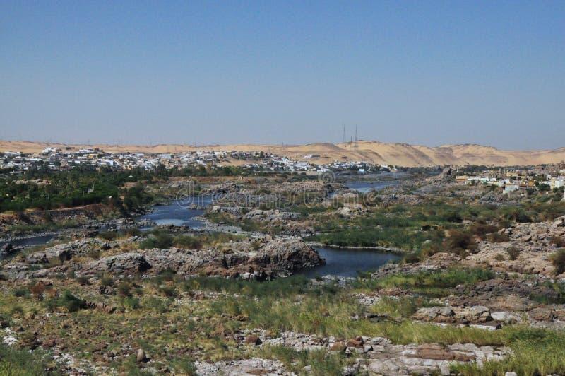 被放弃的小屋和房子由海水与一条含沙道路从山和一些棵树 免版税图库摄影