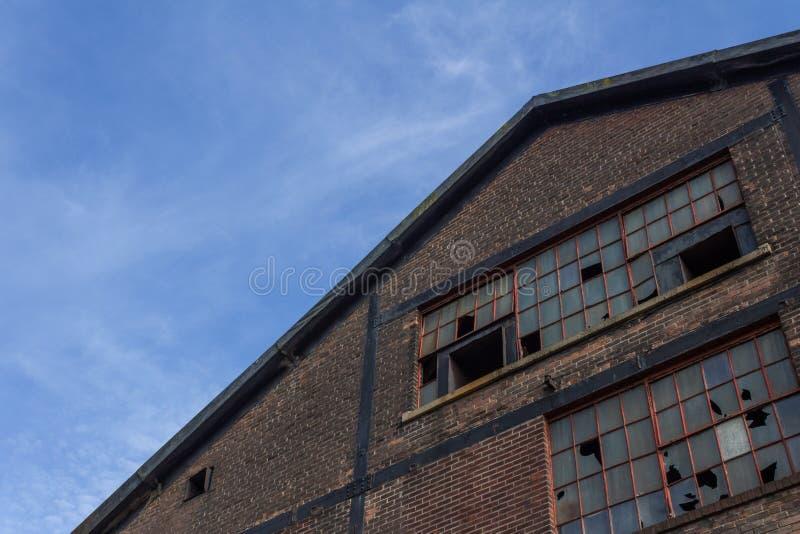 被放弃的工业砖瓦房极端角度图与残破的窗玻璃的 库存照片