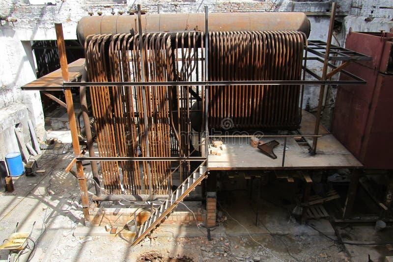 被放弃的工厂厂房内部 老损坏的锅炉室 老生锈的工业管子 老控制中心在锅炉室 免版税库存照片