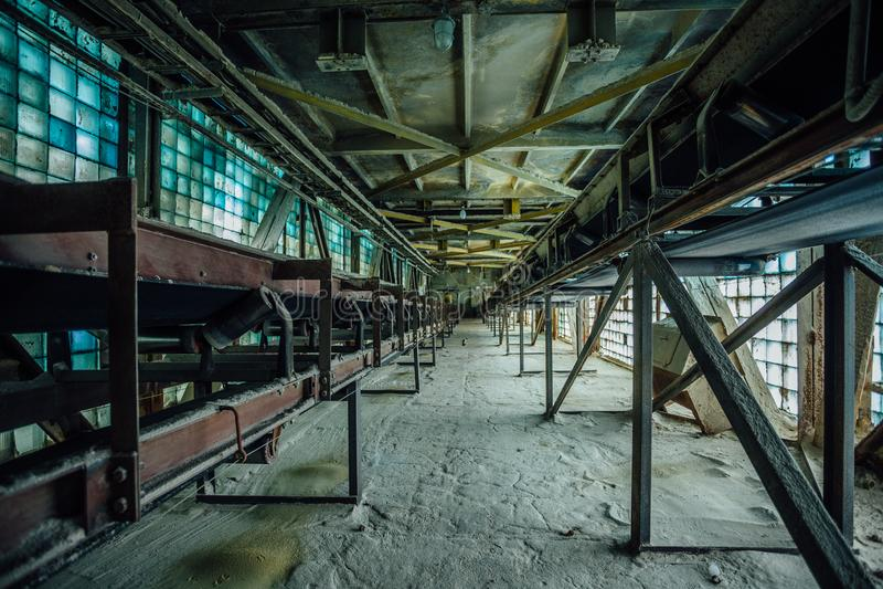 被放弃的工厂 在玻璃砖老走廊的老多灰尘的传送带  免版税库存照片