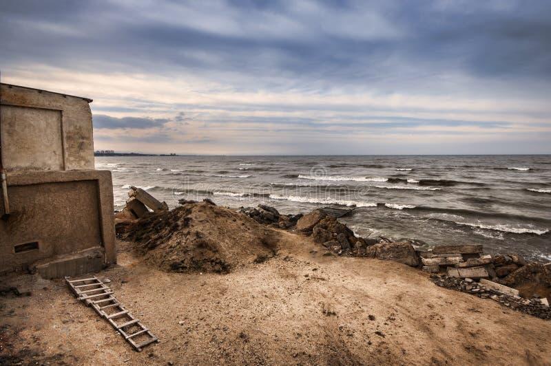 被放弃的房子和梯子美好的超现实的风景在岩石海滨在日落时间 多云天气 里海, Azerbaija 库存照片