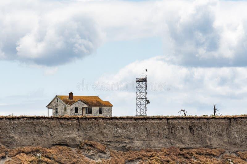 被放弃的房子和通讯台在海岛虚张声势边缘腐蚀和落入Salish海,圣胡安伊斯拉 免版税图库摄影