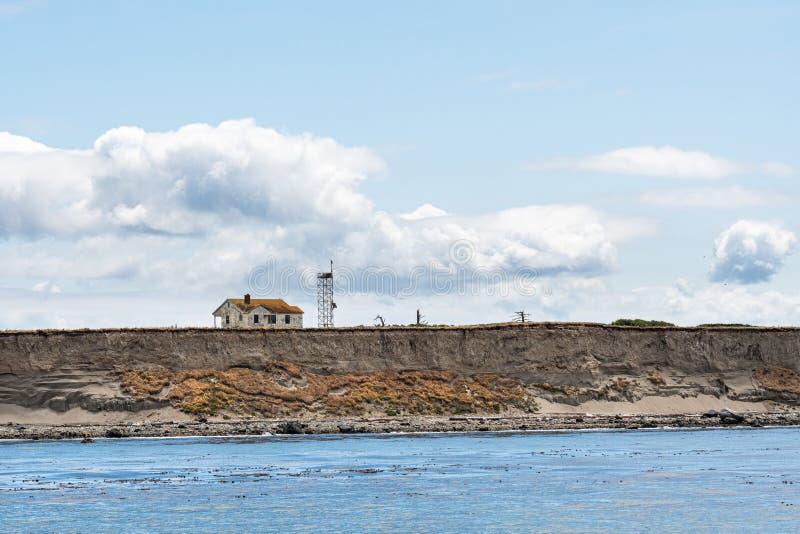 被放弃的房子和通讯台在海岛虚张声势边缘腐蚀和落入Salish海,圣胡安伊斯拉 图库摄影