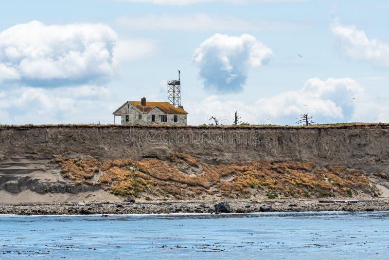 被放弃的房子和通讯台在海岛虚张声势边缘腐蚀和落入Salish海,圣胡安伊斯拉 免版税库存照片