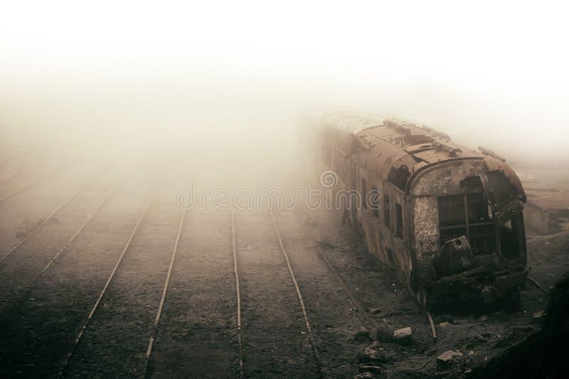 被放弃的生锈的火车和倒空在与超现实和葡萄酒怀乡神色的有薄雾的有雾的天拍摄的火车轨道 免版税库存照片