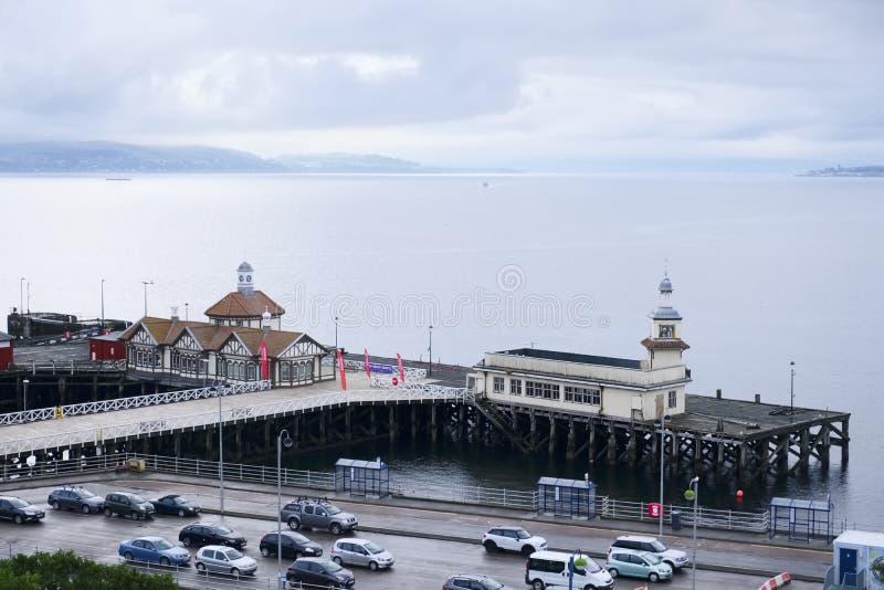 被放弃的码头海沿海维多利亚女王时代的木大厦遗弃云彩浇灌时间间隔Dunoon苏格兰英国 免版税库存照片